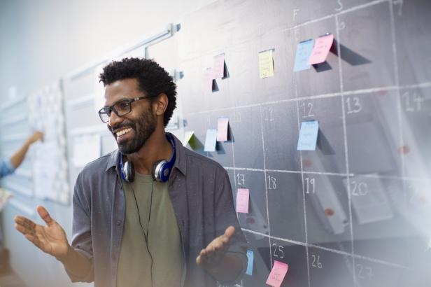 Happy, confident creative businessman planning, scheduling at calendar blackboard